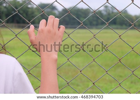 Woman hand grabs the fence