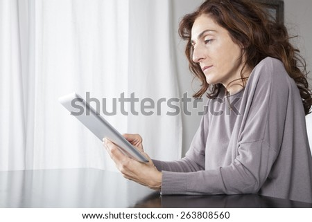 woman hand grey sweater finger touching digital tablet blank screen on black reflect table white curtain indoor
