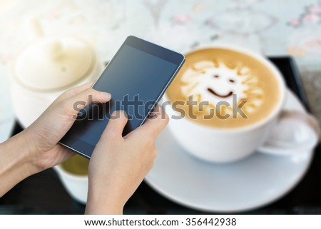 woman hand hold and touch mobile,smart phone,cell phone,tablet,telephone over blurred image of coffee cup at coffee shop - stock photo