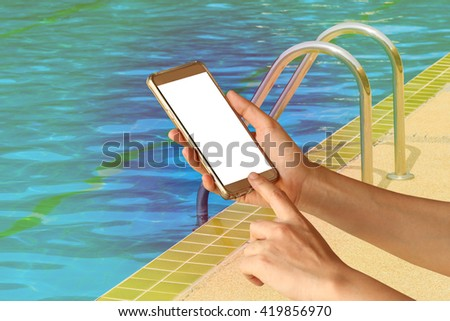 Woman hand hold and touch screen smart phone over ladder of the luxurious swimming pool background - stock photo