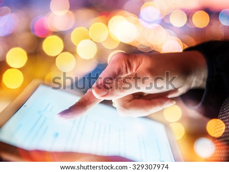 Woman hand hold and touch screen tablet on abstract blurred bokeh of city night light background. Focus in the foreground. - stock photo