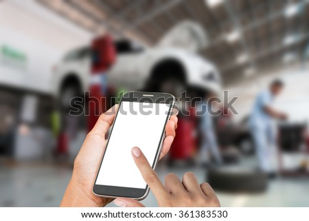 woman hand hold and touch smart phone,cell phone,mobile over blurred image of broken black car : concept calling mechanic service from repair shop - stock photo