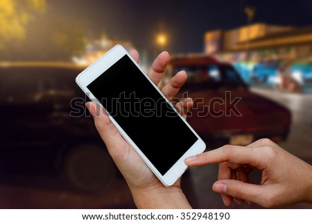 woman hand hold and touch smart phone,cell phone,mobile over blurred image of broken car : calling mechanic service from repair shop and insurance concept - stock photo