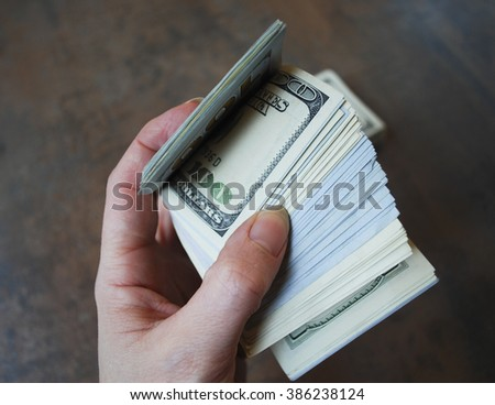 Woman hand hold cash dollar banknotes. Only hundreds.