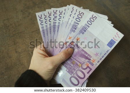 Woman hand hold cash five hundred euro banknotes. - stock photo