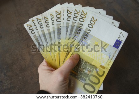 Woman hand hold cash two hundred euro banknotes. - stock photo