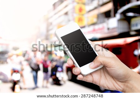 woman hand hold smart phone, tablet,cellphone on blur traffic and people in big market background - stock photo