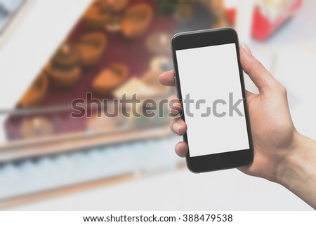 woman hand hold smart phone with blank screen, tablet, cellphone on blur shop background - stock photo