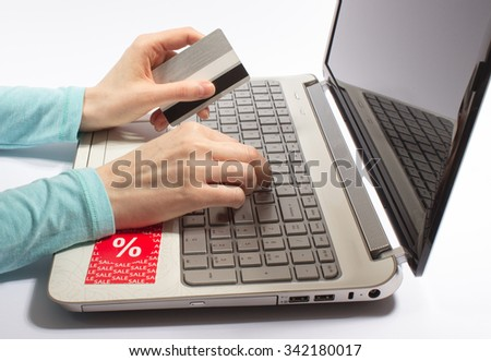 Woman hand holding a credit card and typing. Online shopping on the internet using a laptop.