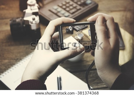 woman hand holding a digital camera on working table - stock photo