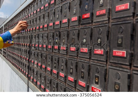 Woman hand holding a key and unlocking a PO box, in the long row of PO boxes