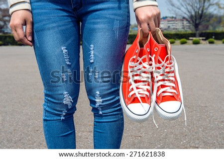 woman hand holding a red sneakers. - stock photo