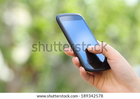 Woman hand holding a smart phone outdoor with a green background - stock photo