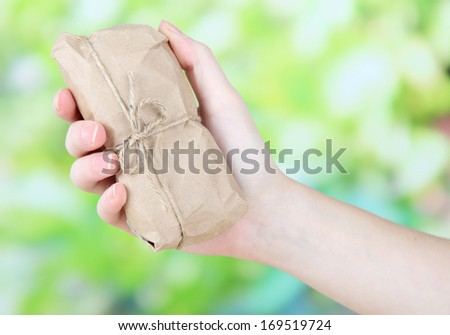 Woman hand holding a telephone wrapped in brown kraft paper, on nature background - stock photo
