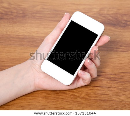 woman hand holding a touch white phone with black screen against the background of a wooden table - stock photo