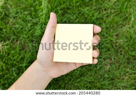 Woman hand holding a yellow notepaper - stock photo
