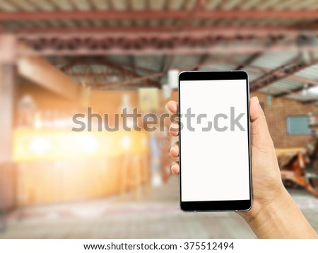 woman hand holding and using the smart phone,mobile on blurred image of coffee shop background,Transactions by smartphone concept - stock photo