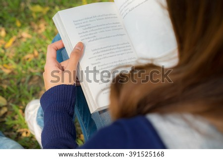 Woman hand holding book in the park.