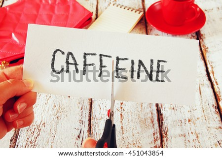 woman hand holding card with the text caffeine, cutting the word. stop or reducing coffee concept. retro style image - stock photo