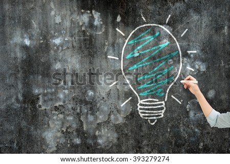 Woman hand holding chalk drawing light bulb on dirty concrete wall. - stock photo