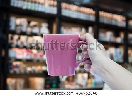 Woman hand holding coffee cup on blurred background, stock photo - stock photo