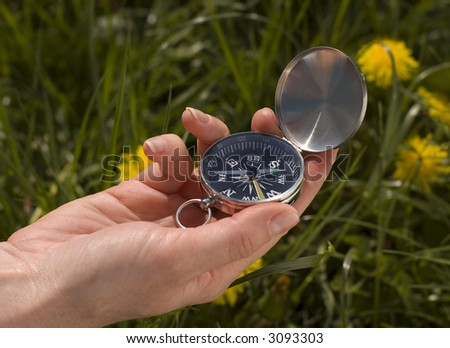 woman hand holding compass outside close up - stock photo