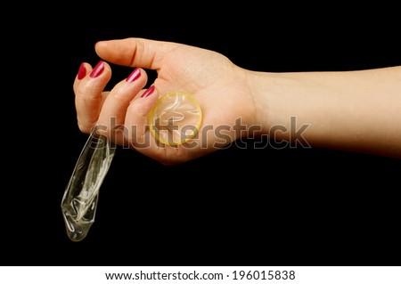 Woman hand holding condom - stock photo