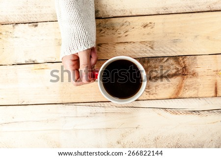 Woman hand holding cup of coffee on old wooden table. - stock photo