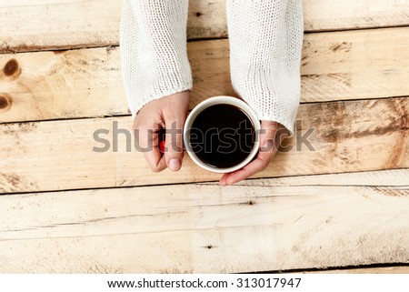 Woman hand holding cup of coffee on old wooden table.