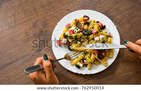 woman hand holding fork and knife with pasta fusilli salad with salami, cheese and olive in white plate on a wooden background. with copy space. top view