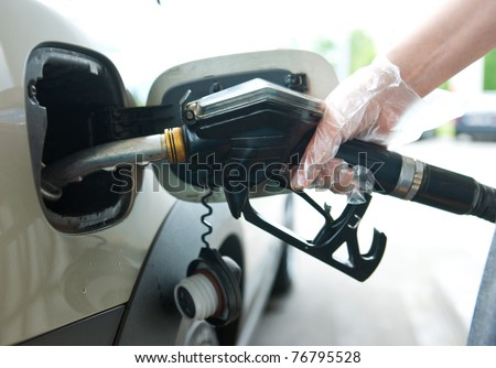woman hand holding fuel nozzle and refuel car in gas station