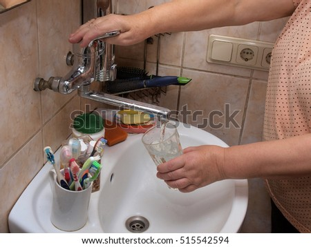 Woman hand holding glass in sink and fill it with water from crane.
