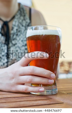 Woman hand holding glass of beer at the pub outside