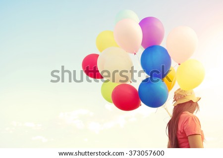 Woman hand holding multicolor balloons done with a vintage pastel filter effect - lifestyle concept in summer holiday - stock photo