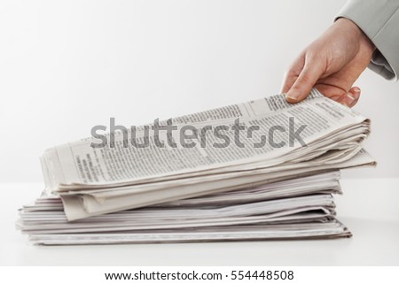 Woman hand holding newspapers on table
