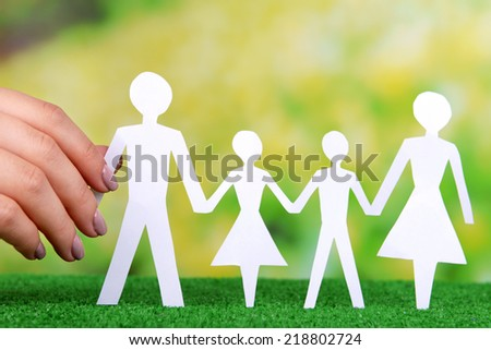 Woman hand holding paper family on grass on bright background - stock photo