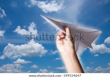 Woman hand holding paper plane,sky background.