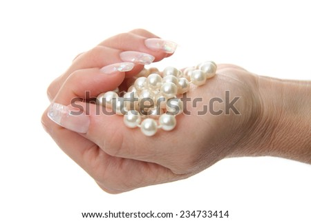 Woman hand holding pearl jewelery - stock photo