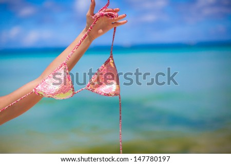 Woman hand holding pink bra isolated on exotic background
