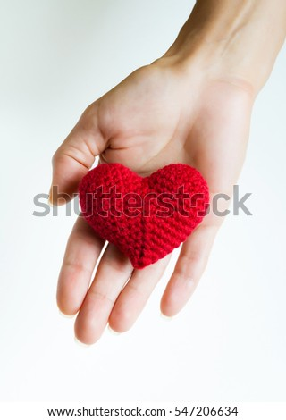 Woman hand holding red crocheted heart. Valentine's Day. Symbol of love.