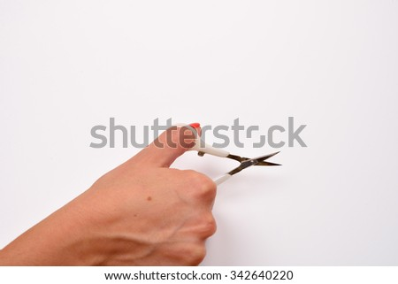 Woman hand holding scissors for manicure on white background. Health and personal care - stock photo
