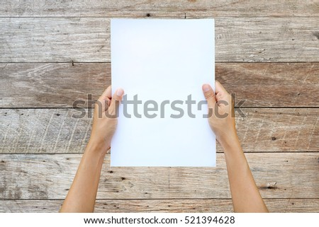 Woman hand holding sheet of paper isolated on wood plank background.