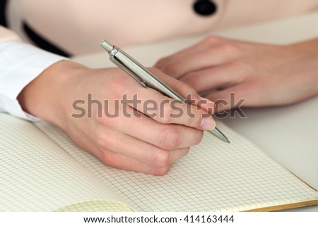 Woman hand holding silver pen ready to make note in opened notebook. Businesswoman or employee at workplace writing business ideas, plans, tasks at personal organizer. Office life or education concept - stock photo