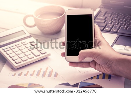 Woman hand holding smart phone,tablet,cellphone and working over desk in the office in vintage color filter - stock photo
