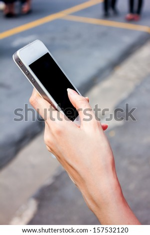 woman hand holding smart phone with street background - stock photo