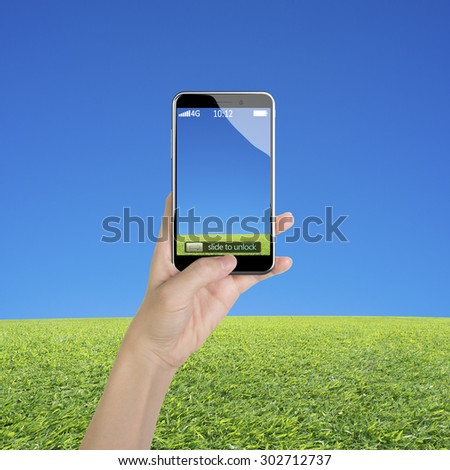 Woman hand holding smart phone, with thumb pushing button, front view, on blue sky and grass background.