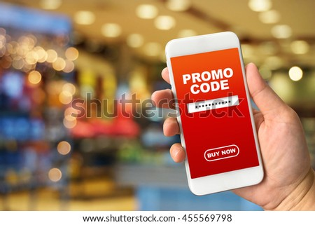 Woman hand holding smartphone against blur bokeh of shop background with word promo code buy now - stock photo