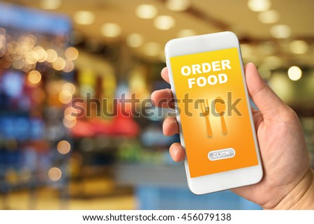Woman hand holding smartphone against blur colorful bokeh background with food online concept - stock photo
