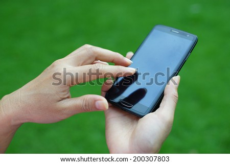 Woman hand holding smartphone against green background