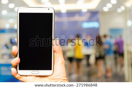 Woman hand holding smartphone against on blured of background soft focus. - stock photo